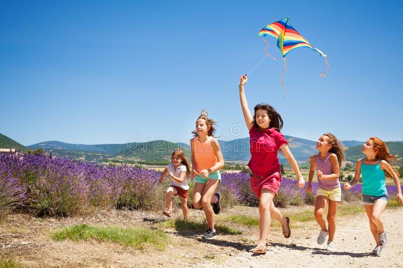 Kids flying kite running through lavender field. Group of happy age-diverse kids flying colorful kite running through lavender field stock image