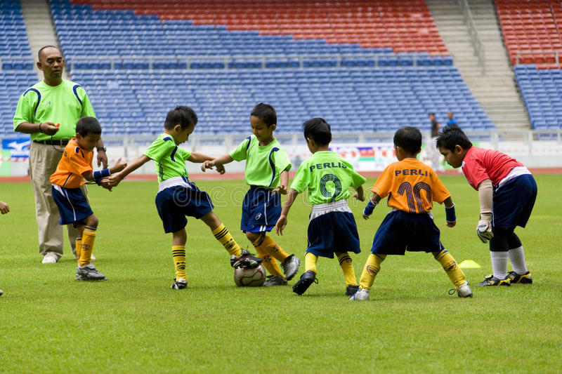 Kids Football Action. Image of kids playing soccer as part of the opening ceremony of the Malaysian Amateur Athletic Union Open Championships 2007 held at the stock photo