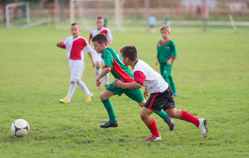 Kids football match. Kids running with ball on football match royalty free stock photos
