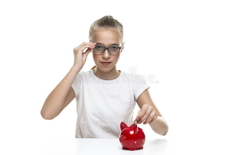Kids Frugal Concepts. Blond Teenager Girl Posing With Coins and Piggy Bank. Storing up Money With Moneybox For Savings. Horizontal image royalty free stock images