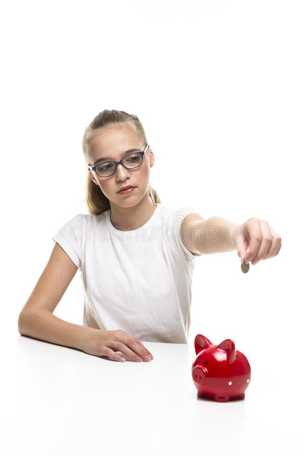 Kids Frugal Concepts. Blond Teenager Girl Posing With Coins and Piggy Bank. Storing up Money With Moneybox For Savings. Vertical Image royalty free stock images