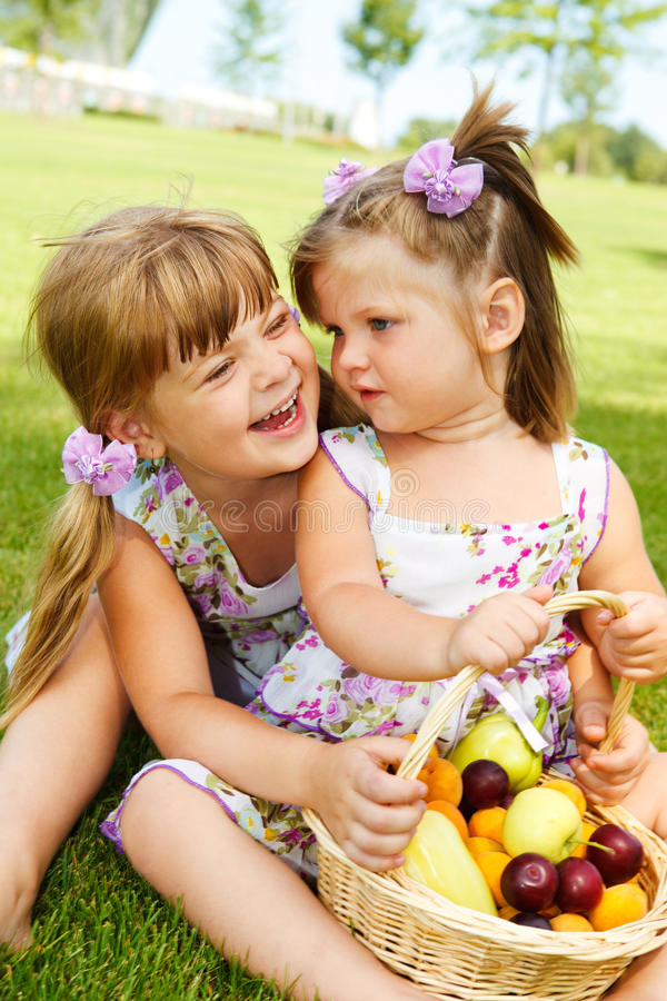 Kids with fruit basket. Laughing kids sit with fruit basket in the garden royalty free stock photography
