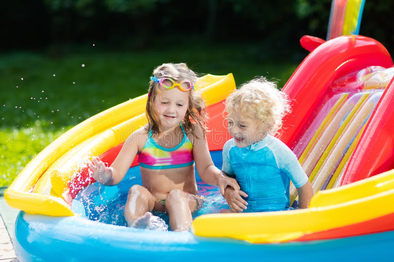 Kids in garden swimming pool with slide stock photo