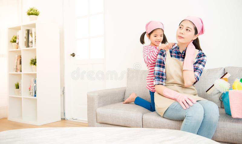 Kids girl helping tired mother massage. Happy asian chinese kids girl helping tired mother massage and doing the cleaning in living room together at home royalty free stock photos