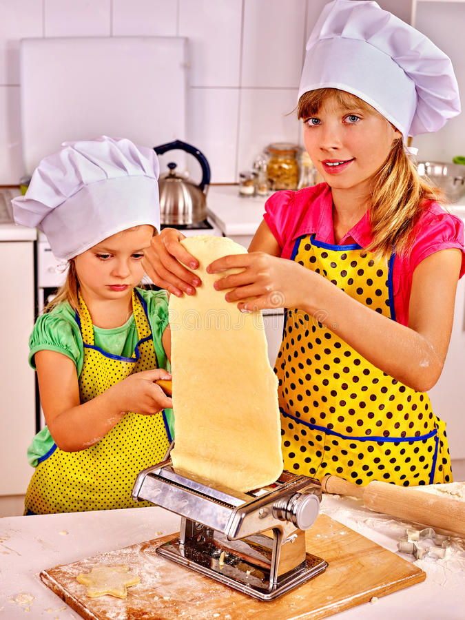 Kids girl making homemade pasta at kitchen royalty free stock photos