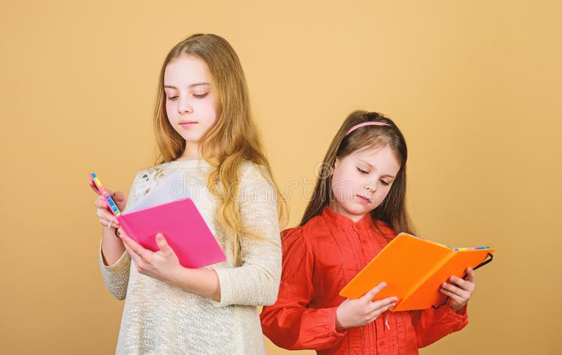 Kids girls with books or notepads. Education and kids literature. Favorite fairytale. Sisters pick books to read royalty free stock image