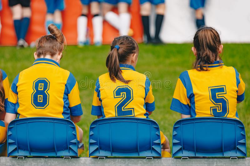 Kids girls elementary school sports team sitting on bench on the grass field. Soccer football junior girls team. At sports outdoor field before match royalty free stock photos