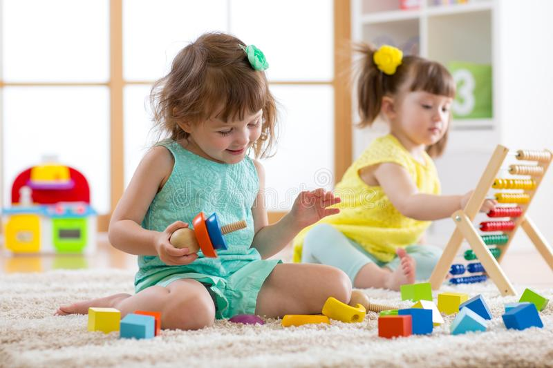 Kids are engaging in daycare. Two toddler children playing with educational toys in kindergarten. stock photos
