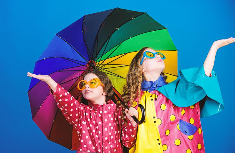 Kids girls happy friends under umbrella. Bright umbrella. Happy childhood. It is easier to be happy together. Be rainbow stock images