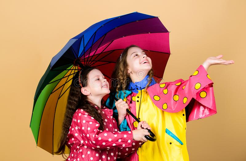 Kids girls happy friends under umbrella. Rainy weather with proper garments. Bright umbrella. It is easier to be happy. Together. Be rainbow in someones cloud royalty free stock images