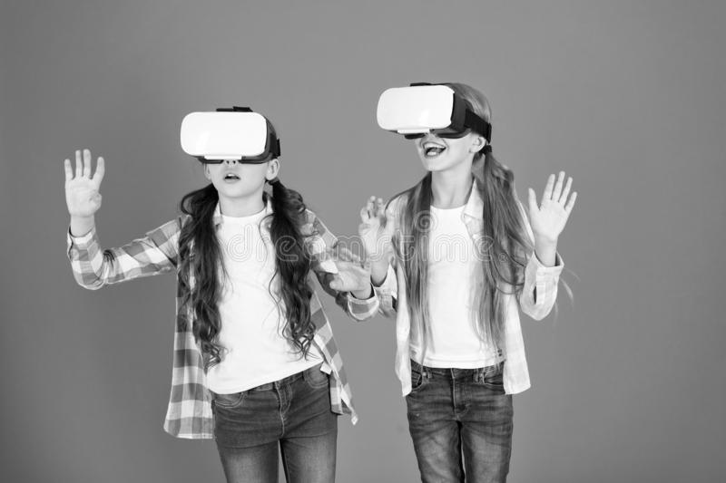Kids girls play virtual reality game. Friends interact in vr. Explore alternative reality. Future is present. Cyber. Space and virtual gaming. Virtual reality stock image