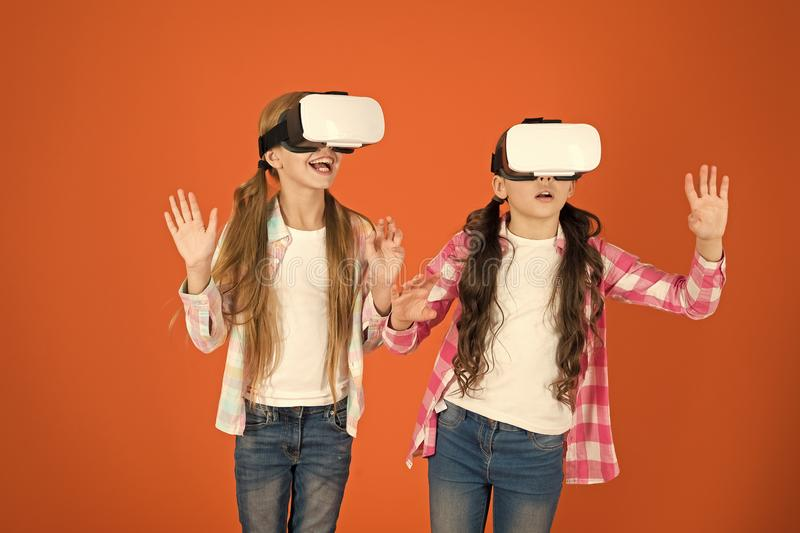 Kids girls play virtual reality game. Friends interact in vr. Explore alternative reality. Future is present. Cyber. Space and virtual gaming. Virtual reality royalty free stock photography