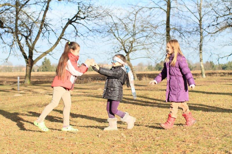 Kids - girls playing blind man's buff stock images