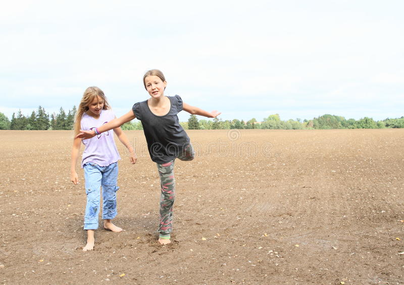 Kids - girls standing on field. Little kids - barefoot girls standing on ground of muddy field and exercising royalty free stock images