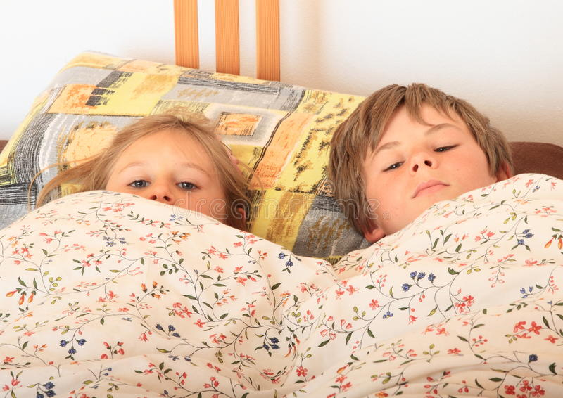 Kids going to sleep. Two kids - boy and girl lying in a bed on pillow under blanket with flowers and going to sleep stock photo