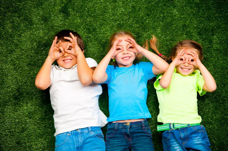 Kids on grass. Small kids lie on the green grass stock images