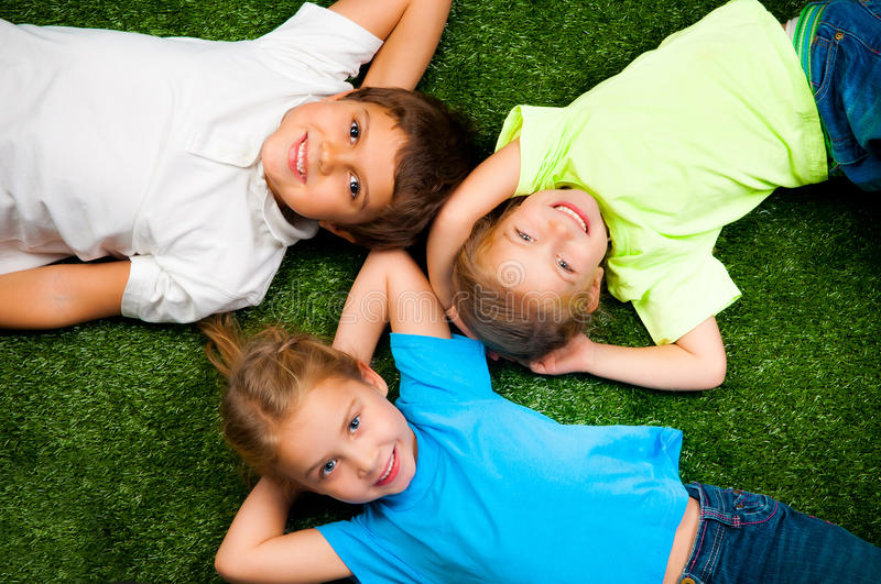 Kids on grass. Small kids lie on the green grass royalty free stock image