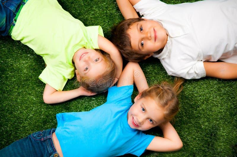 Kids on grass. Small kids lie on the green grass stock photos