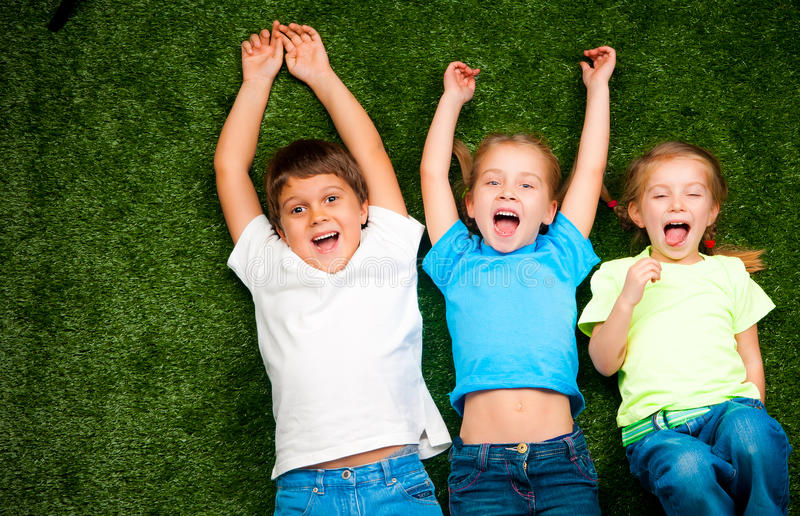 Kids on grass. Small kids lie on the green grass royalty free stock photos