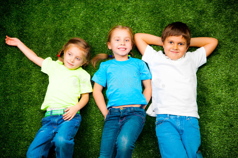 Kids on grass. Small kids lie on the green grass stock image