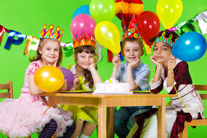 Kids group and birthday cake. Kids group sitting at the table with the birthday cake royalty free stock image