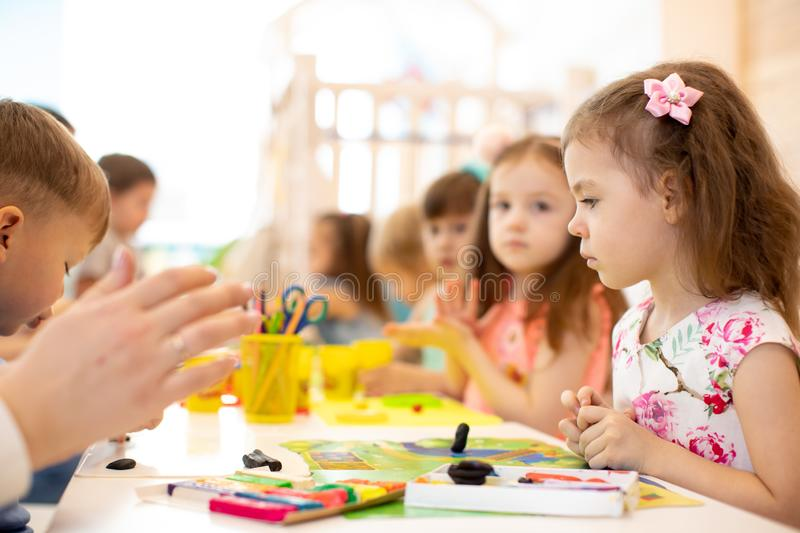 Kids group learning arts and crafts in daycare centre stock image
