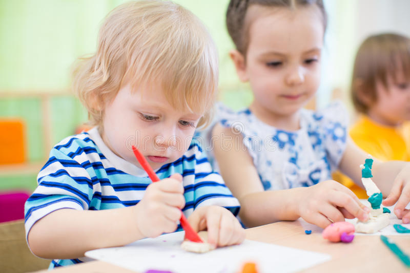 Kids group learning arts and crafts in kindergarten together royalty free stock photography