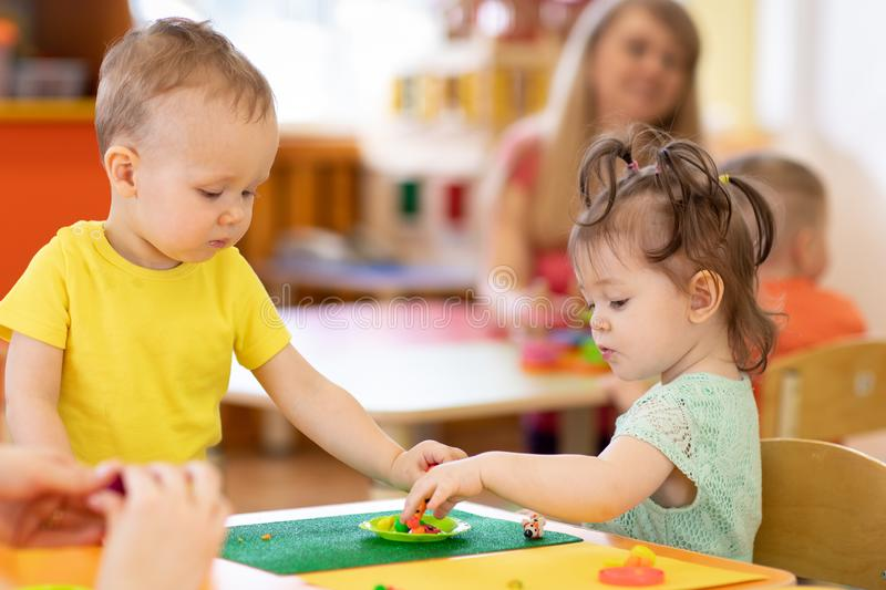 Kids group making arts and crafts in kindergarten. Children on lesson in daycare centre stock image