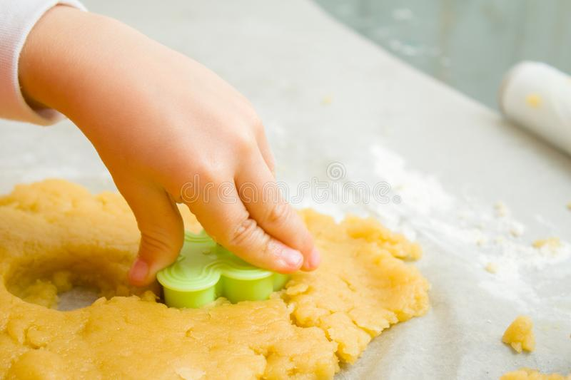 Kids hand with form of christmas cookies for children, making gingerbread in form of man. New year treat for Santa Claus cooking. royalty free stock photos