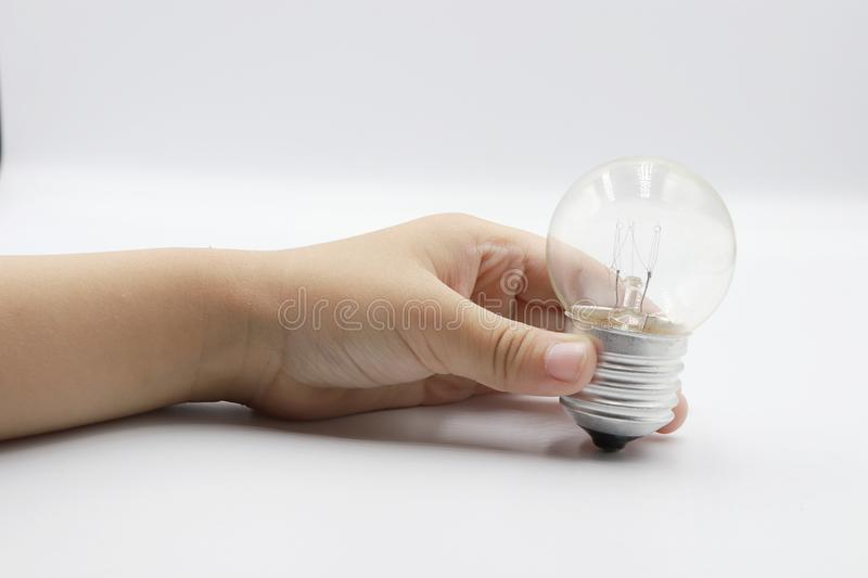 Kids hand holding a light bulb isolated on white background stock photography