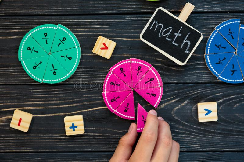 Kids hand moves colorful math fractions on dark wooden background or table. Interesting creative funny math for kids. Education, back to school concept royalty free stock images