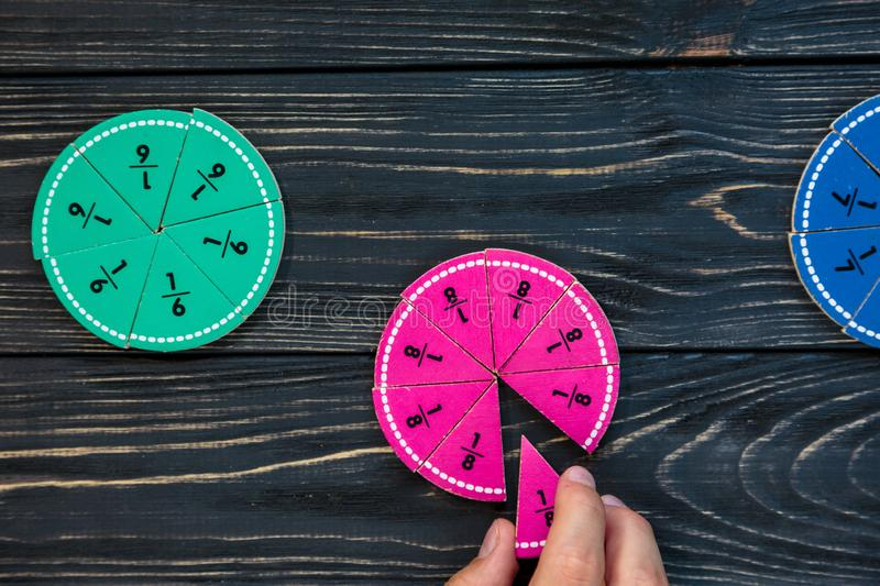 Kids hand moves colorful math fractions on dark wooden background or table. Interesting creative funny math for kids. Education. Back to school concept royalty free stock photo