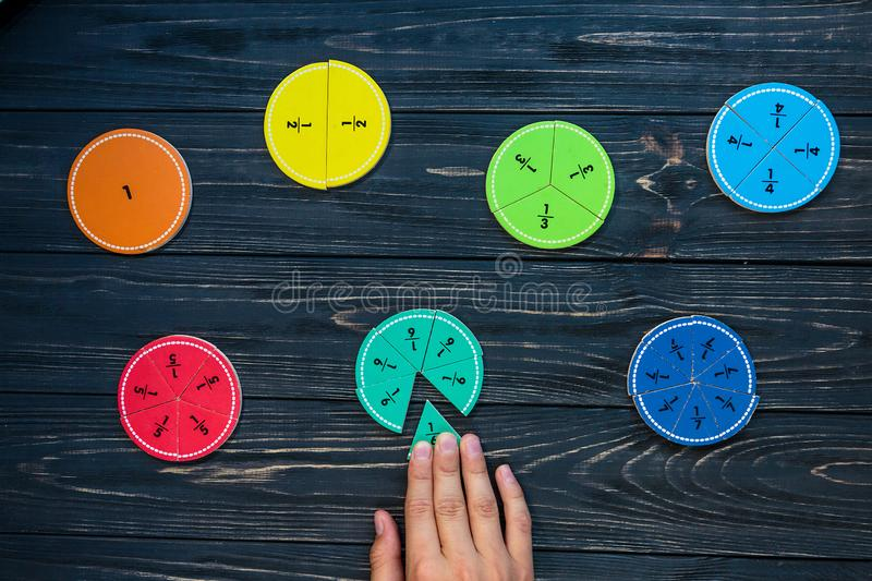 Kids hand moves colorful math fractions on dark wooden background or table. Interesting creative funny math for kids. Education, back to school concept royalty free stock image