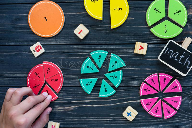 Kids hand moves colorful math fractions on dark wooden background or table. Interesting creative funny math for kids. Education, back to school concept stock photos