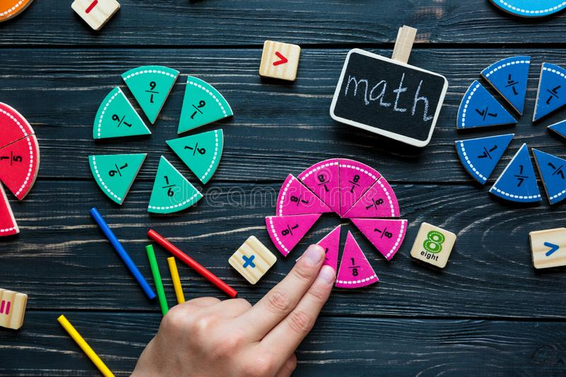 Kids hand moves colorful math fractions on dark wooden background or table. Interesting creative funny math for kids. Education. Back to school concept royalty free stock image