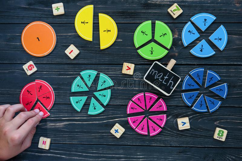 Kids hand moves colorful math fractions on dark wooden background or table. Interesting creative funny math for kids. Education. Back to school concept stock photography