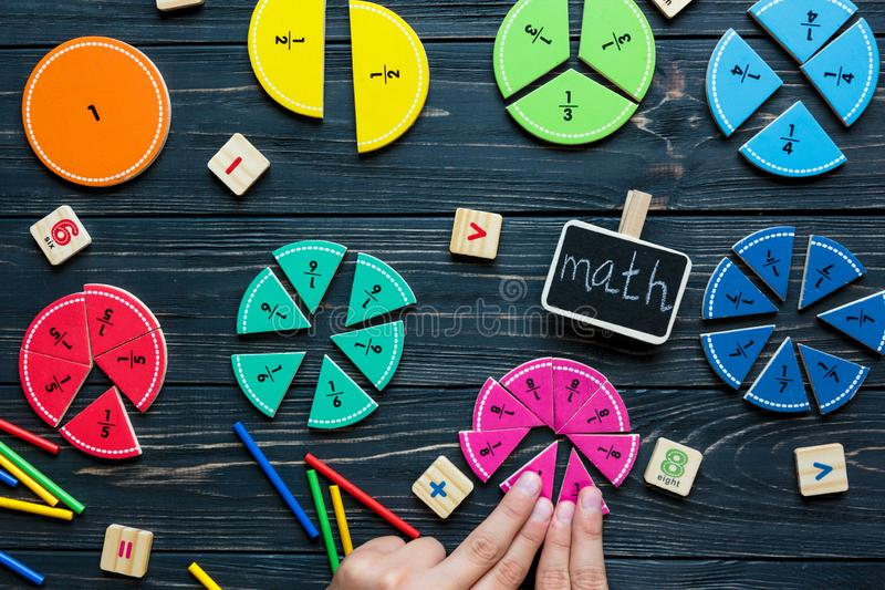 Kids hand moves colorful math fractions on dark wooden background or table. Interesting creative funny math for kids. Education. Back to school concept stock photos