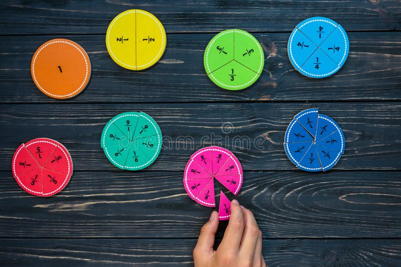 Kids hand moves colorful math fractions on dark wooden background or table. Interesting creative funny math for kids. Education, back to school concept stock photography