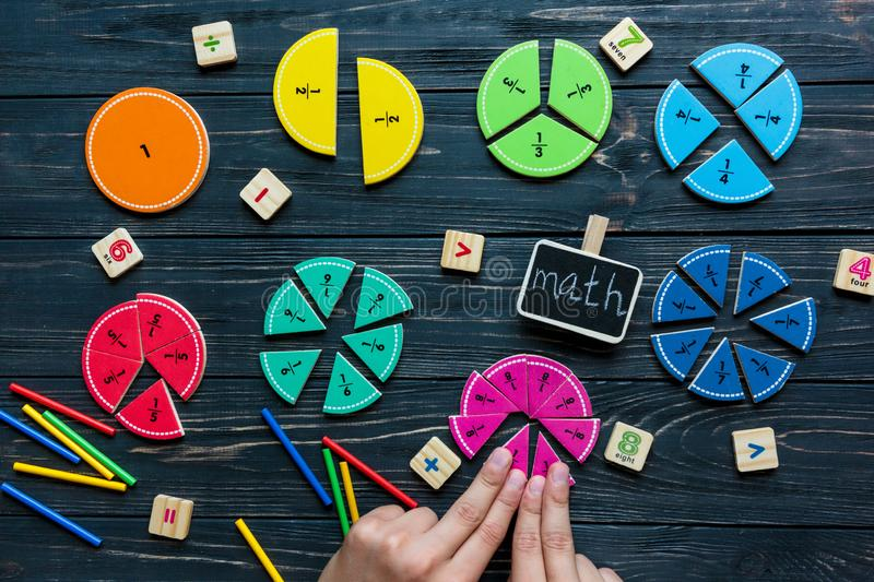 Kids hand moves colorful math fractions on dark wooden background or table. Interesting creative funny math for kids. Education, back to school concept stock images