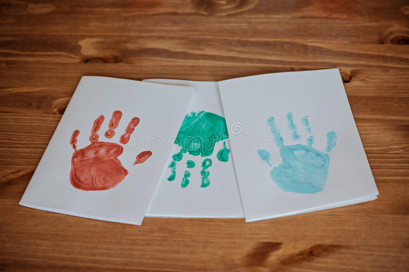 Kids handprints post cards blanks on wooden table. Kids colored handprints post cards blanks on wooden table royalty free stock photo