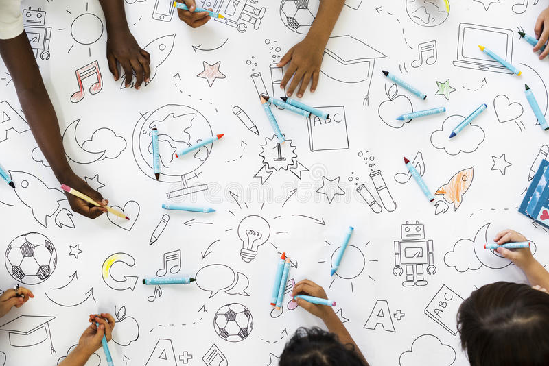 Kids hands holding colored pencils painting on art drawing paper royalty free stock photos