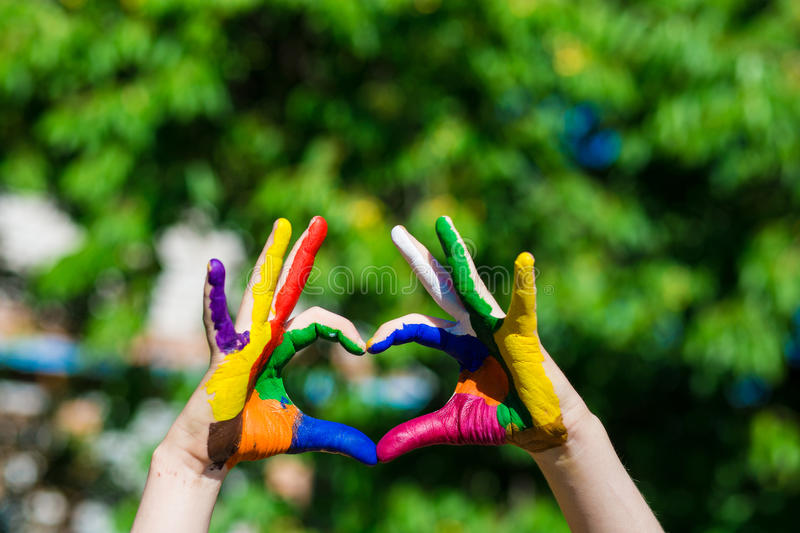 Kids hands painted in bright colors make a heart shape on summer nature background. Kids hands painted in bright colors make a heart shape on nature background royalty free stock photo