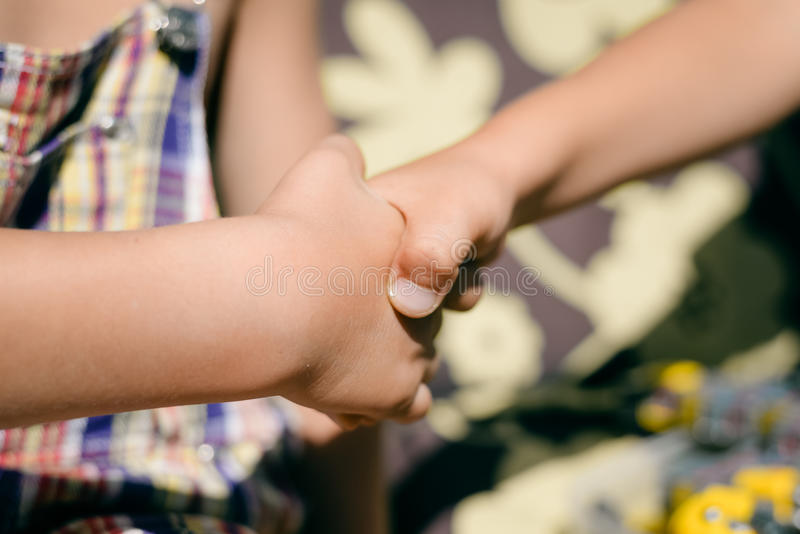 Kids handshake closeup on sunny outdoors background stock photos