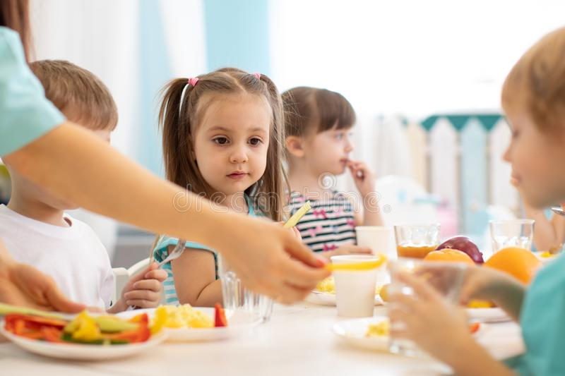 Kids have a dinner in preschool. Little boys and girls from the group of children sit at table with lunch and eat royalty free stock image