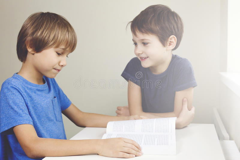 Kids have fun reading a book. Boy reads a story to his brother at home stock image