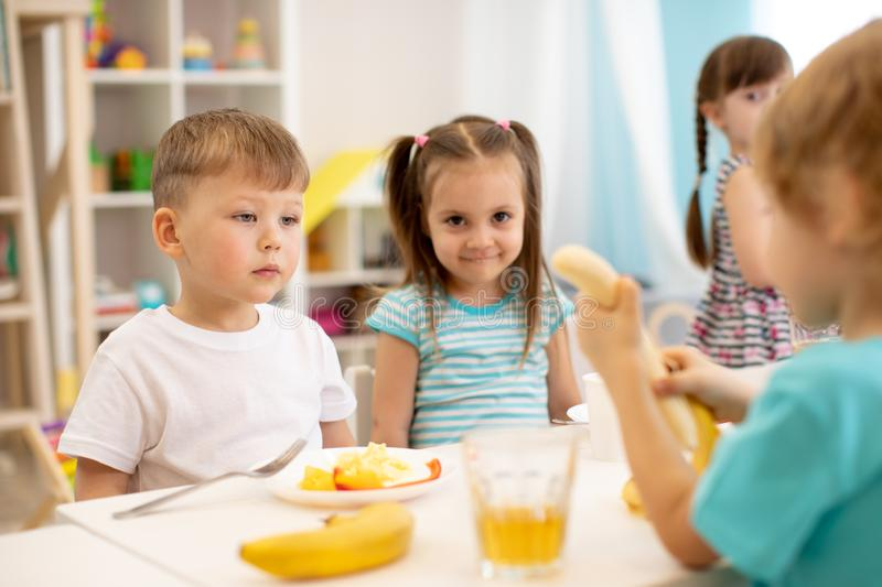 Kids have a lunch in daycare centre. Children eat fresh fruits in kindergarten royalty free stock image