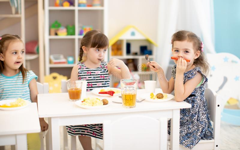 Kids have a lunch in daycare centre. Children eating healthy food in kindergarten. Little girl have fun showing mustache stock images
