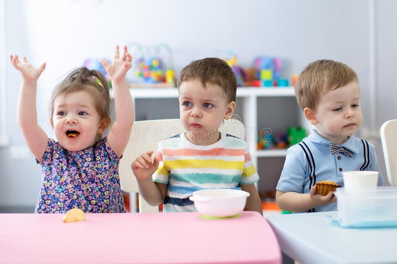 Kids have a lunch in daycare centre. Children eating in kindergarten royalty free stock photos