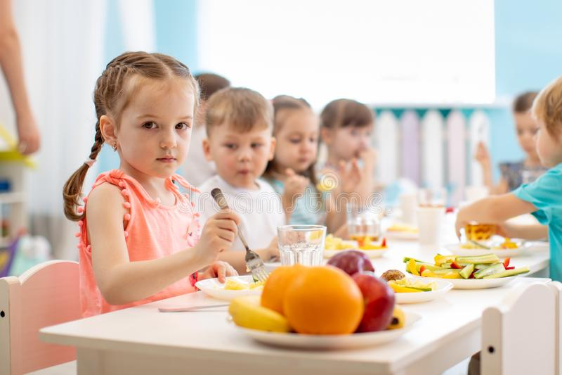 Kids have lunch in daycare. Children eat healthy food in kindergarten stock photos