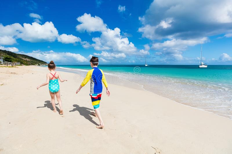 Kids having fun at beach. Kids brother and sister walking at tropical beach during Caribbean summer vacation royalty free stock photo
